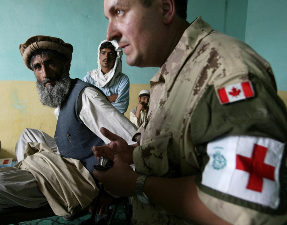 Military Dr. Americo Rodrigues., 42, of Toronto administers to a patient at a frontier clinic in Mala Mahmed Khil, Afghanistan, on Wednesday, May 20, 2004. (CP PHOTO/Stephen Thorne)