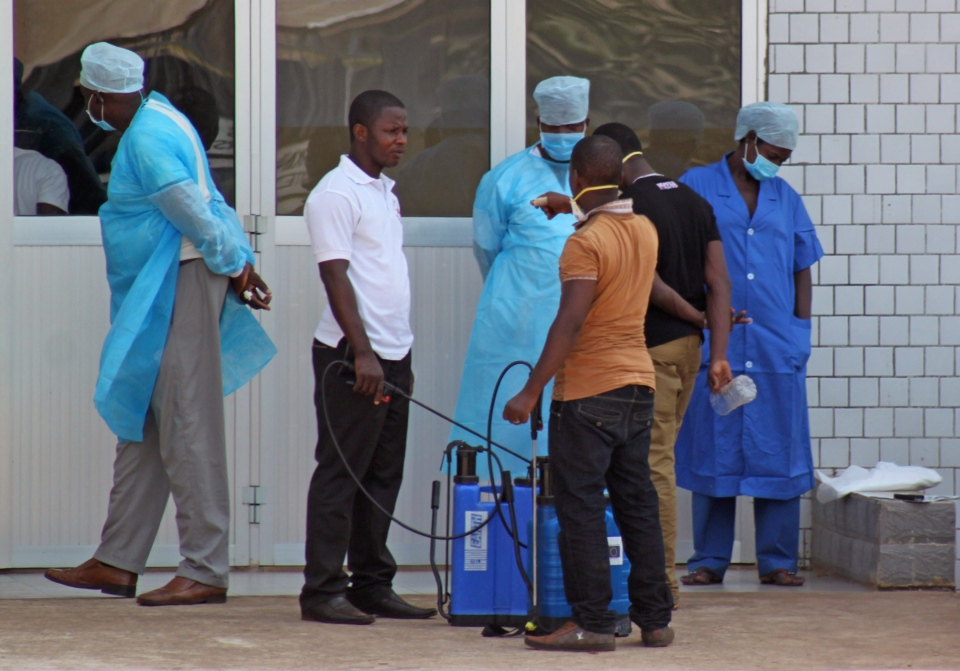 In this photo taken on Saturday, March 29, 2014, medical personnel at the emergency entrance of a hospital receive suspected Ebola virus patients in Conakry, Guinea. (AP Photo/ Youssouf Bah)