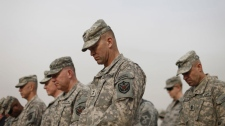 Military personnel lower their heads during ceremonies of the encasing of the US Forces Iraq colors, in Baghdad, Iraq, Thursday, Dec., 15, 2011.