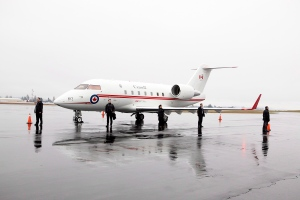 Prime Minister Stephen Harper's security staff looks over the Challenger jet during his arrival at the Shell Aerocentre during his Western tour in North Saanich, B.C., Tuesday, Jan. 7, 2014. (Chad Hipolito / THE CANADIAN PRESS)