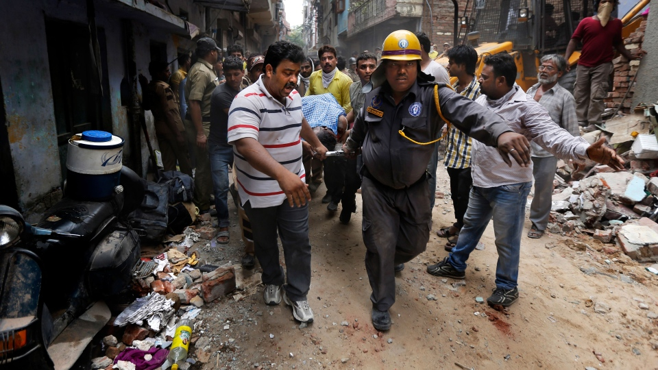 Rescue workers carry the body of a victim amid the debris of a building that collapsed in New Delhi, India, Saturday, June 28, 2014. (AP / Altaf Qadri)