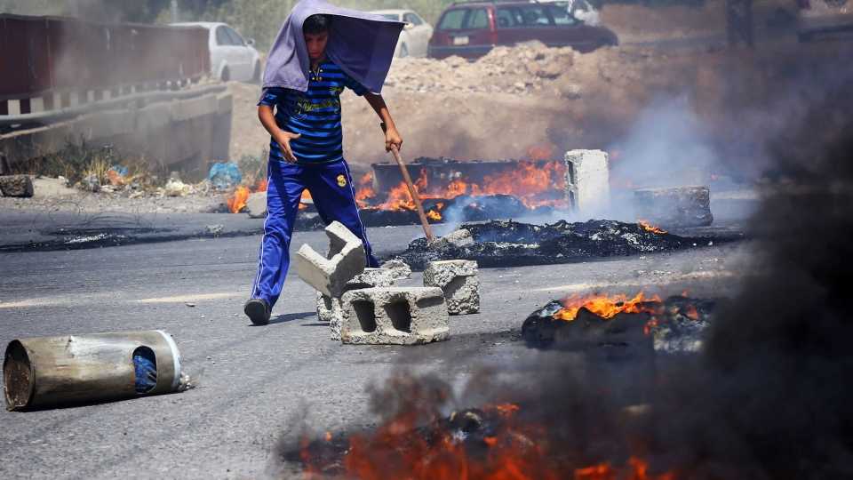 An Iraqi Kurd helps block a road during a demonstration against the fuel crisis in Irbil, Iraq, Sunday, June 29, 2014. (AP)