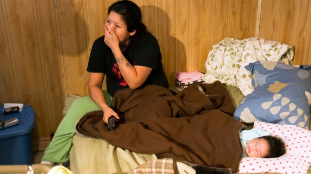 Lee Kamalatisit and her two-month-old daughter Kaylee sit in their unserviced, one-room home in Attawapiskat, Ont., Saturday, Dec. 17, 2011. (Frank Gunn / THE CANADIAN PRESS)