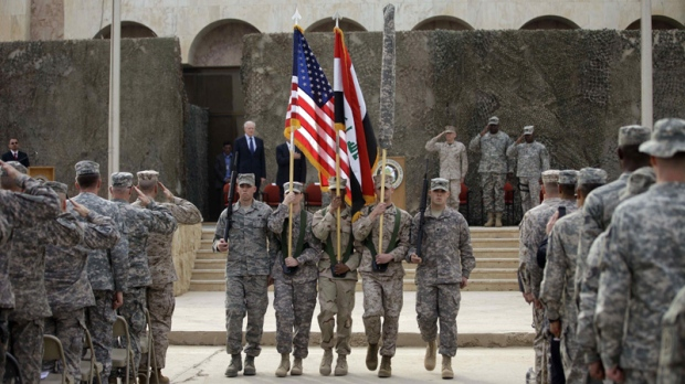 The US flag, Iraq flag, and the U.S. Forces-Iraq colors are carried during ceremonies marking the end of US military mission in Baghdad, Iraq, Thursday, Dec. 15, 2011. (AP Photo/Khalid Mohammed)
