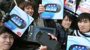 People show off their newly purchased PlayStation Vita portable games in Tokyo Saturday, Dec. 17, 2011. (AP Photo/Kyodo News)