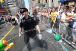 A police officer is sprayed by parade goers during the WorldPride Parade in Toronto, Sunday, June 29, 2014. (Kevin Van Paassen  / THE CANADIAN PRESS)