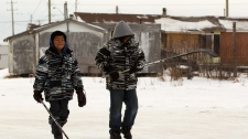Two young boys walk past substandard housing on their way to play hockey in Attawapiskat, Ont. Saturday, Dec. 17, 2011. (Frank Gunn / THE CANADIAN PRESS)