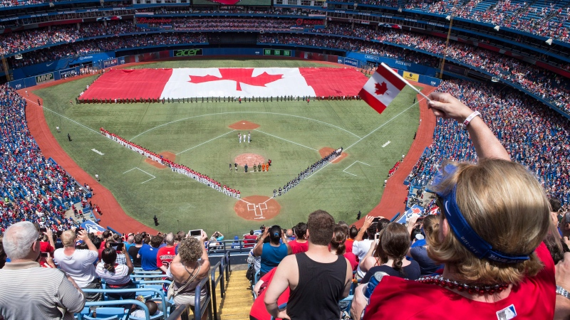 A Canadian flag is unveiled on the field before the Toronto Blue Jays take on the Milwaukee Brewers in interleague baseball action as they mark Canada Day in Toronto on Tuesday July 1 , 2014. (Chris Young / THE CANADIAN PRESS)