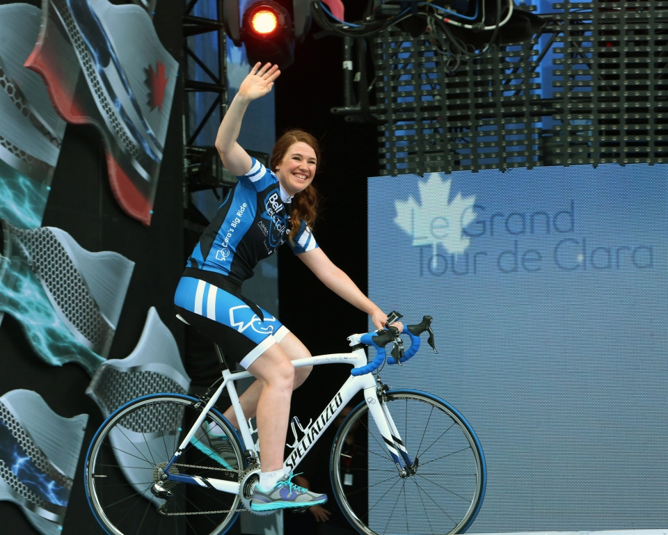 Olympic athlete Clara Hughes waves on stage as she completes her cross Canada tour during Canada Day celebrations on Parliament Hill in Ottawa, Tuesday, July 1, 2014. (Fred Chartrand / THE CANADIAN PRESS)