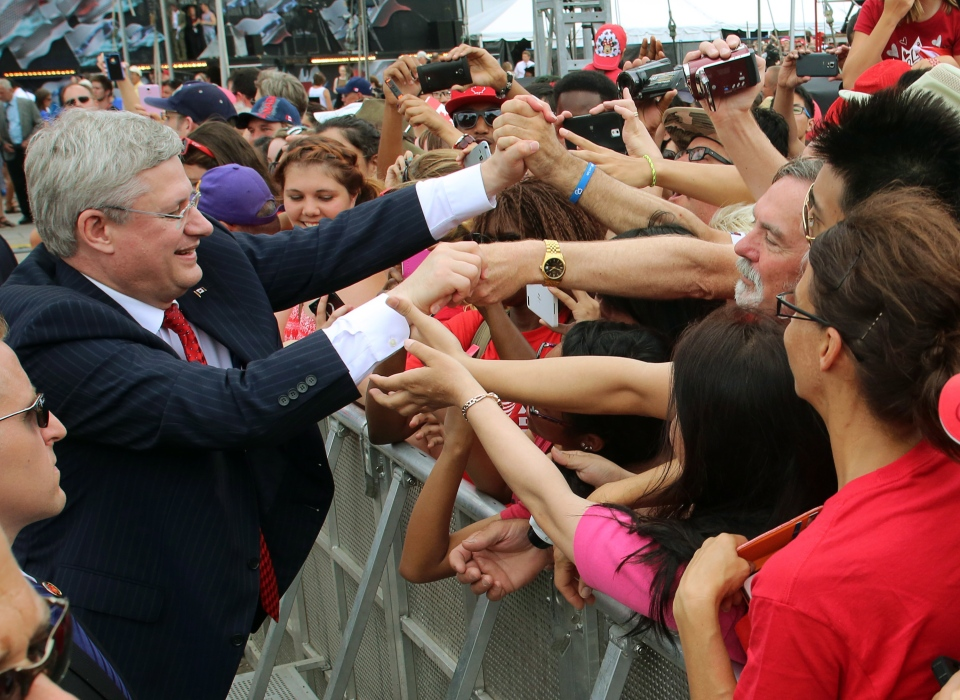 Prime Minister Stephen Harper shakes hands with people during Canada Day celebrations on Parliament Hill in Ottawa, Tuesday, July 1, 2014. (Fred Chartrand / THE CANADIAN PRESS)