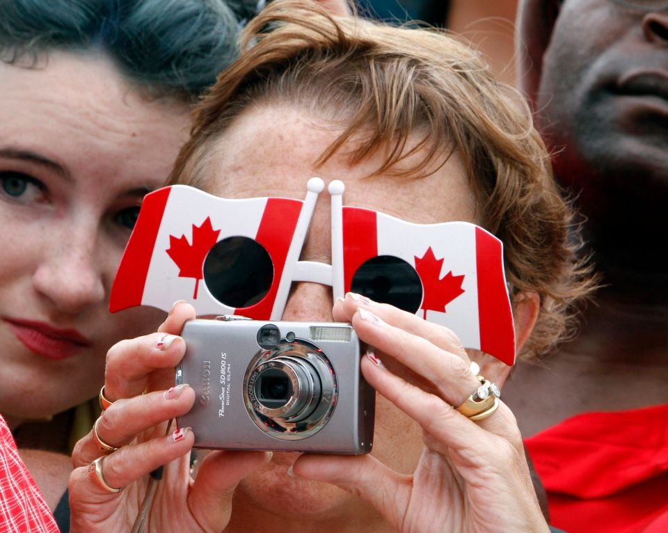 A woman wearing Canadian flag-shaped sunglasses takes a photo while taking part in celebrations on Parliament Hill in Ottawa, Tuesday, July 1, 2014. (Fred Chartrand / THE CANADIAN PRESS)