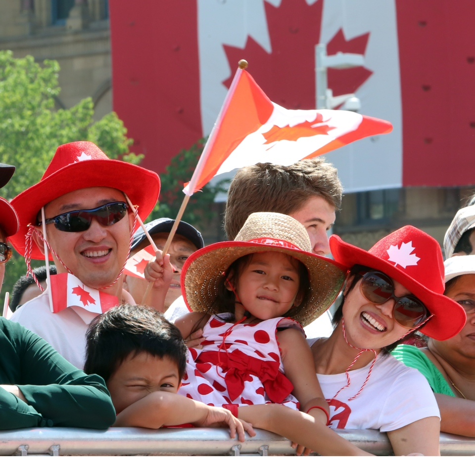Ron Liu along with his six-year-old son Robbie, four-year-old daughter Elaine and his wife May, take part in Canada Day celebrations on Parliament Hill in Ottawa, Tuesday, July 1, 2014. (Fred Chartrand / THE CANADIAN PRESS)