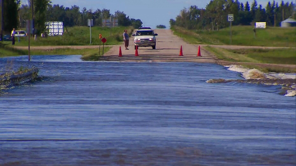 A truck stops before a washed out road in Melville, Saskatchewan, Tuesday, July 1, 2014.