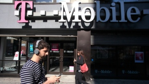 This Sept. 12, 2012 file photo shows a man using a cellphone as he passes a T-Mobile store in New York. (Mark Lennihan)