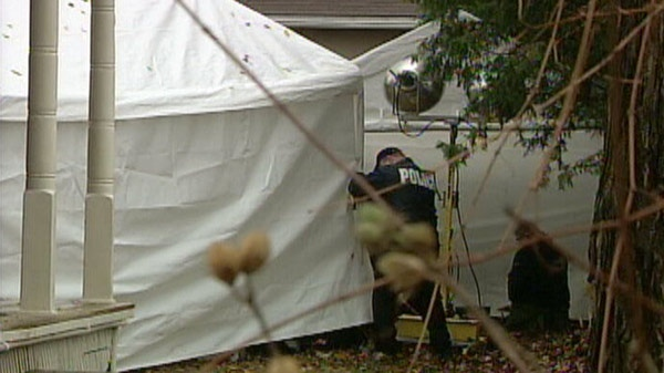Police investigate after the remains of Clifford Fair were found behind a Woodstock, Ont. home in 2008.