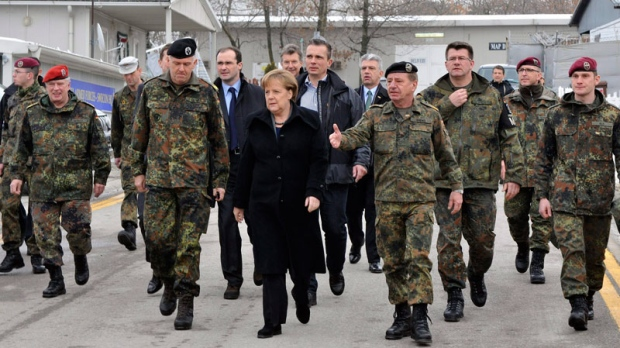German Chancellor Angela Merkel, center, is escorted by KFOR Commander Erhard Drews, fourth from right, as she visits German soldiers during her visit to KFOR headquarters in Pristina, Kosovo, Monday, Dec. 19, 2011. (AP / Visar Kryeziu)