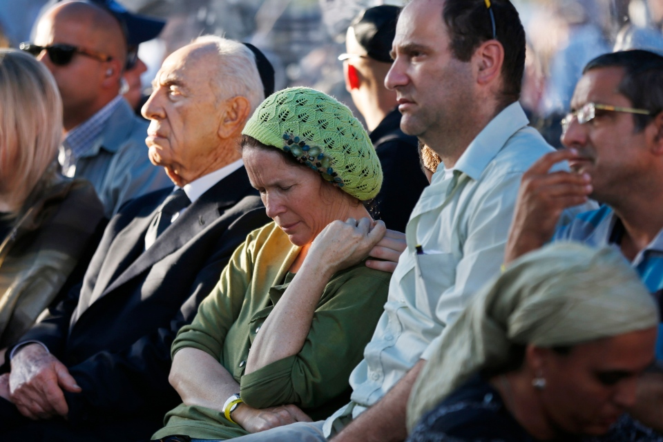 Rachel and Avi Fraenkel, parents of U.S.-Israeli national Naftali, 16, one of the three Israeli teens who were abducted and killed in the West Bank, mourn as they sit next to Israeli President Shimon Peres during their son's joint funeral in the Israeli city of Modiin, Tuesday, July 1, 2014. (AP / Baz Ratner)