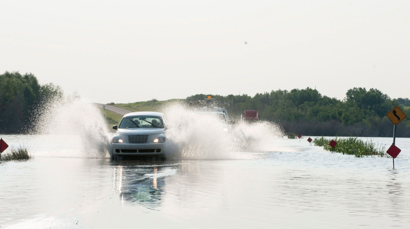 Vehicles drive over a submerged section of Highway 5 near Humboldt, Sask. on Wednesday, July 2, 2014. (Liam Richards / THE CANADIAN PRESS)