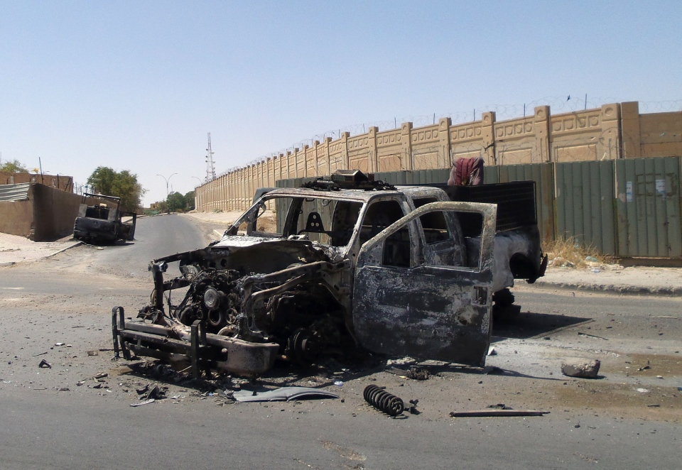 Destroyed police trucks are shown on Tuesday, July 1, 2014, after clashes between fighters of the al Qaeda-inspired Islamic State of Iraq and the Levant and Iraqi security forces in central Tikrit, Iraq. (AP Photo)