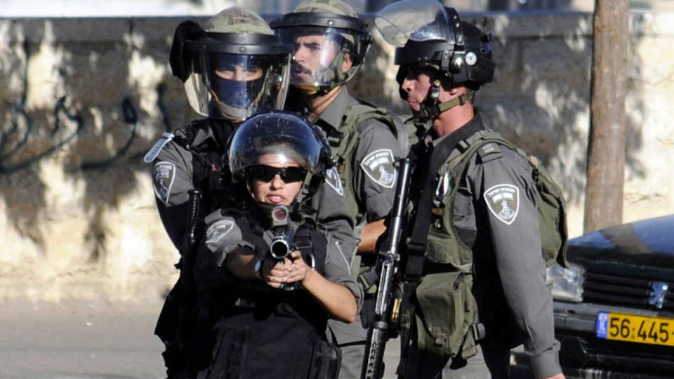 An Israeli border police woman aims her weapon during clashes with Palestinians in Jerusalem on Wednesday, July 2, 2014. (AP / Mahmoud Illean)