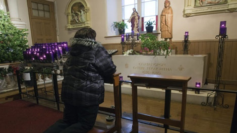 A woman prays at the tomb of Kateri Tekakwitha at St. Francis Xavier Church Monday, December 19, 2011 in Kahnawake, Que, south of Montreal. Tekakwitha was born in 1656 and has been placed on the list for cannonization by the Vatican.THE CANADIAN PRESS/Ryan Remiorz