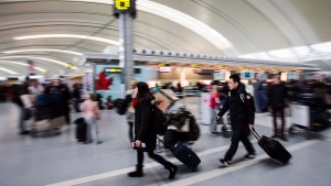 People carry luggage at Pearson International Airport in Toronto on Friday, December 20, 2013. (Mark Blinch / THE CANADIAN PRESS)