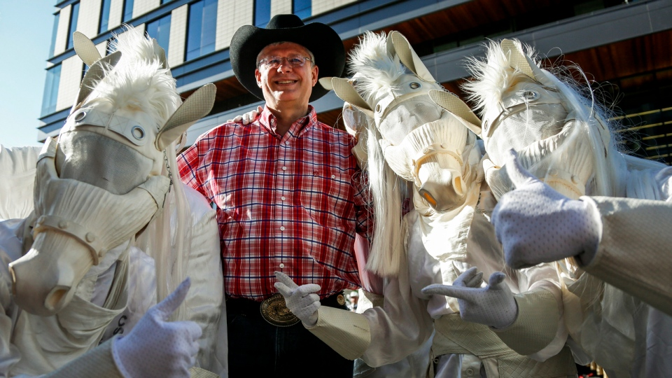 Prime Minister Stephen Harper poses with people dressed as horses at the Calgary Stampede parade, Friday, July 4, 2014. (Jeff McIntosh / THE CANADIAN PRESS)