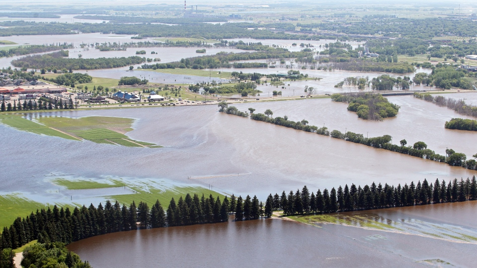 The swollen Assiniboine River spills over its banks covering farm land in Brandon, Man. on Sunday, July 6, 2014. (Tim Smith / THE CANADIAN PRESS)