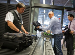 Passengers queue at the security checkpoint at the Rhein-Main airport in Frankfurt, Germany, Thursday July 3, 2014. (AP Photo/dpa,Frank Rumpenhorst)