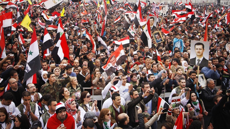 Pro-regime protesters chant slogans during a rally at Umayyad Square in Damascus, Syria, Wednesday, Dec. 21, 2011. (AP Photo/ Muzaffar Salman)