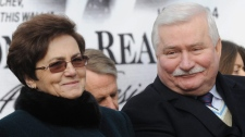 Former Polish President Lech Walesa and wife Danuta smile during an unveiling ceremony of a statue honoring the late U.S. president Ronald Reagan, in Warsaw, Poland, Monday, Nov. 21, 2011.