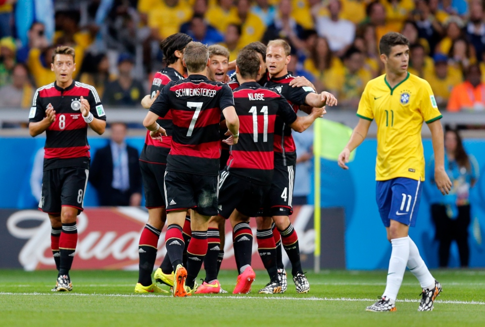 Brazil's Oscar, right, passes by celebrating German players after Germany's Thomas Mueller scored the opening goal during the World Cup semifinal soccer match between Brazil and Germany at the Mineirao Stadium in Belo Horizonte, Brazil, Tuesday, July 8, 2014. (AP / Frank Augstein)