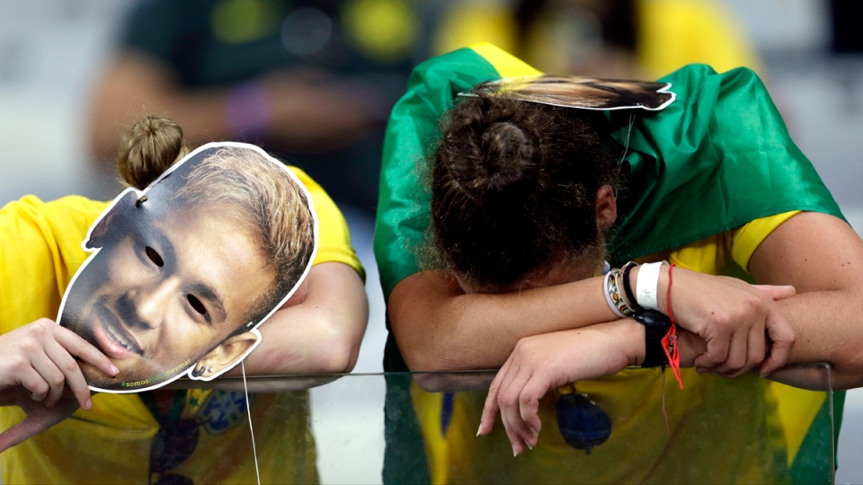 Brazilian supporters holding Neymar face masks react after Germany defeated Brazil 7-1 to advance to the finals during the World Cup semifinal soccer match between Brazil and Germany at the Mineirao Stadium in Belo Horizonte, Brazil, Tuesday, July 8, 2014. (AP / Andre Penner)