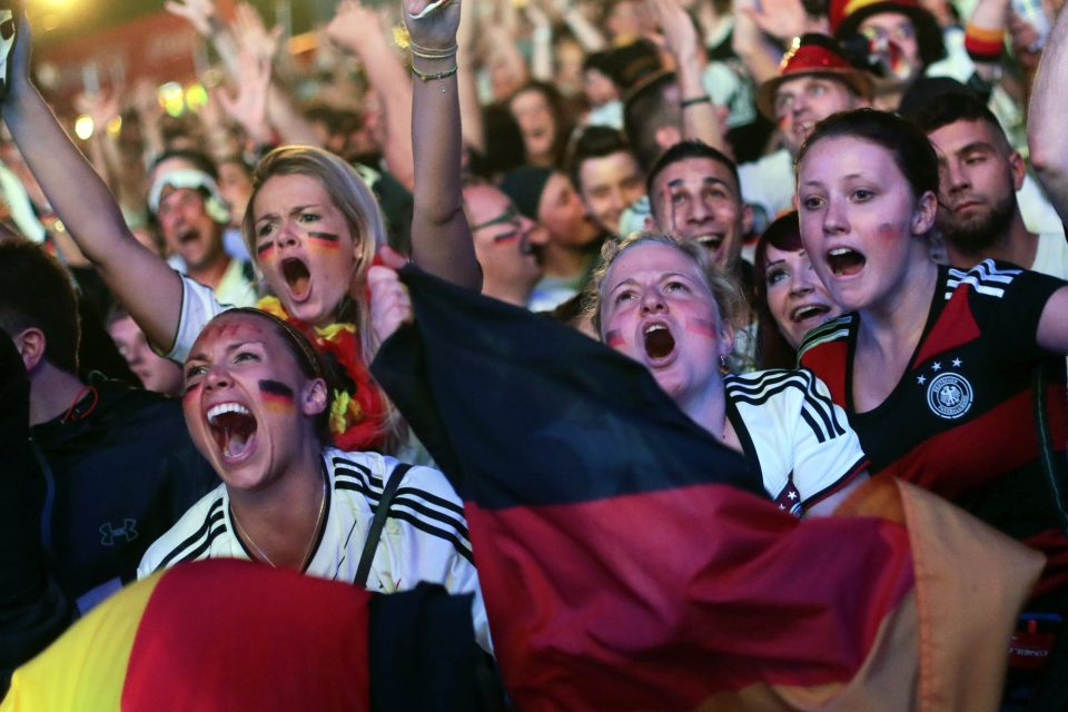 German soccer fans celebrate after their team won the Brazil World Cup semi final being played in Belo Horizonte, Brazil, between Germany and Brazil at a public viewing event called 'Fan Mile' in Berlin, Tuesday, July 8, 2014. (AP / Markus Schreiber)