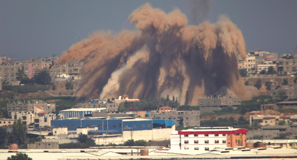 Smoke and debris rise after an Israeli strike on the Gaza Strip, visible from the Israeli side of the border, Wednesday, July 9, 2014. (AP / Ariel Schalit)