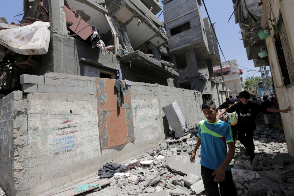 Palestinians walk through rubble of a building belonging to a senior Hamas official that was damaged in an Israeli missile strike in the Jabaliya refugee camp in the northern Gaza Strip, Wednesday, July 9, 2014. (AP / Adel Hana)