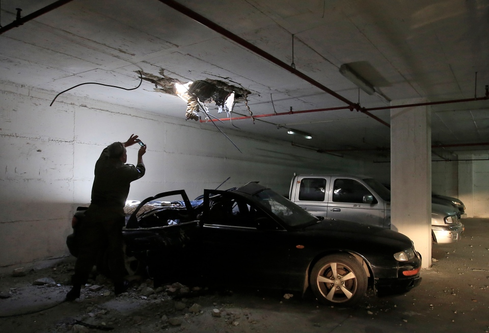 An Israeli army officer photographs the impact of a rocket fired from the Gaza strip in an underground parking lot in Ashdod, Israel, Wednesday, July 9, 2014. (AP / Tsafrir Abayov)