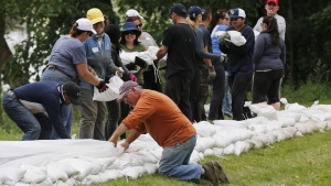 Volunteers help sandbag in St. Francois Xavier, Man., Tuesday, July 8, 2014. (John Woods / THE CANADIAN PRESS)
