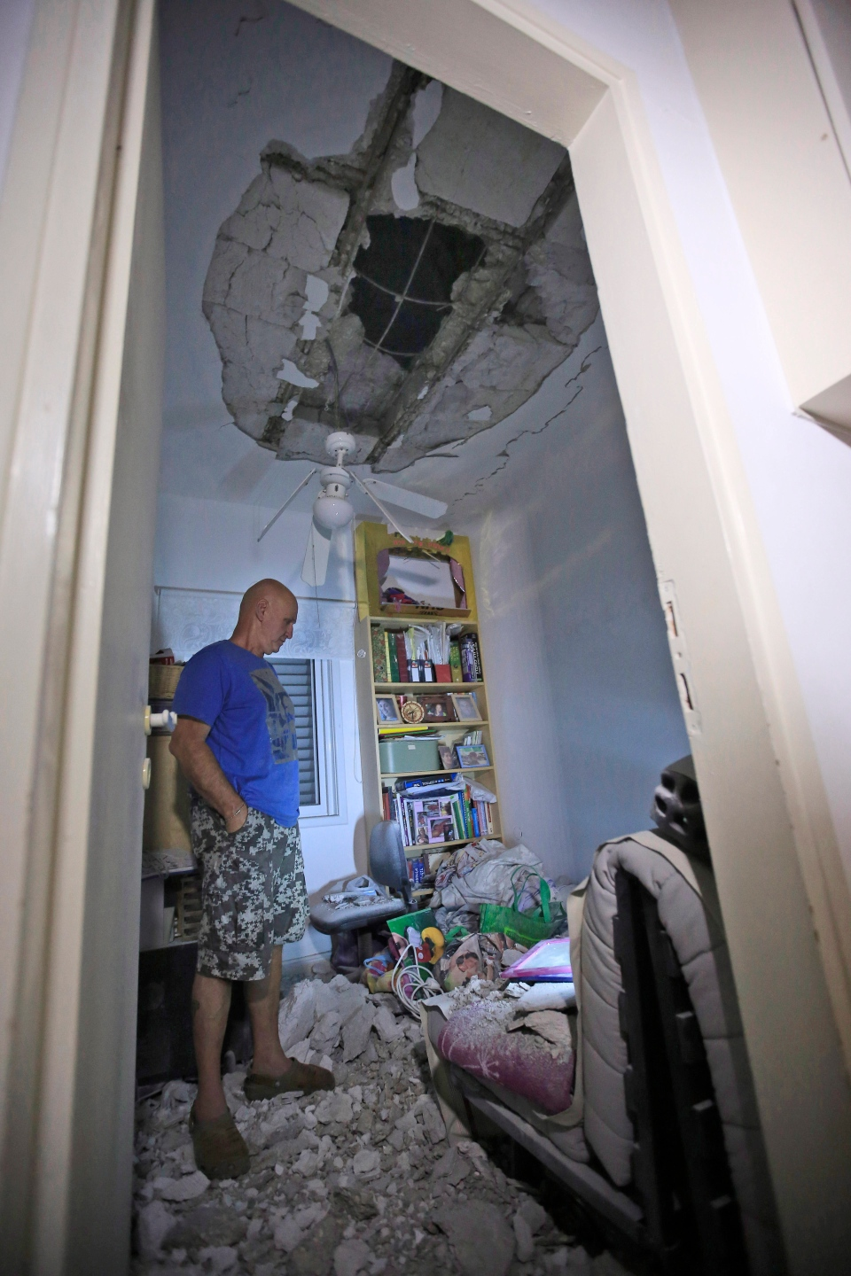 An Israeli looks at damage to his home from a rocket attack in a kibbutz near border with the Gaza Strip on Wednesday, July 9, 2014. (AP / Tsafrir Abayov)