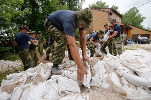 Soldiers from 17 Wing in Winnipeg sandbag in St. Francois Xavier, Man., Tuesday, July 8, 2014. Several days of frantic sandbagging is paying off in southern Manitoba as a crest of flood water is expected to pour through the region. (John Woods/THE CANADIAN PRESS)