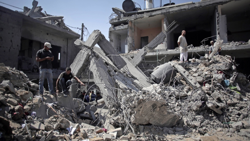 Palestinians search in the rubble of a destroyed house where eight members of the Al Haj family were killed in a strike early morning in Khan Younis refugee camp, southern Gaza Strip on Thursday, July 10, 2014. (AP / Khalil Hamra)