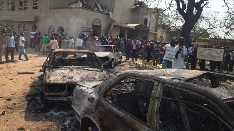 Onlookers gather around a destroyed car at the site of a bomb blast at St. Theresa Catholic Church in Madalla, Nigeria, Sunday, Dec. 25, 2011.
