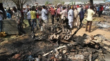 Onlookers gather around a car destroyed in a blast next to St. Theresa Catholic Church in Madalla, Nigeria, Sunday, Dec. 25, 2011.