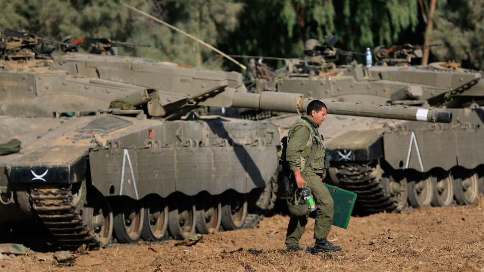 An Israeli soldier walks past tanks near the Israel and Gaza border, Thursday, July 10, 2014. (AP / Tsafrir Abayov)