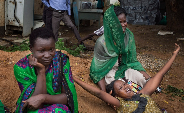 Relatives of Samual Moro, 30, grieve after he died of cholera, outside the cholera isolation ward at the Juba Teaching Hospital in the capital Juba, South Sudan, Saturday, May 24, 2014. (AP Photo/Matthew Abbott)