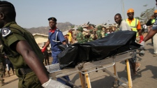 Rescue workers push a dead body after a bomb blast at St. Theresa Catholic Church in Madalla, Nigeria, Sunday, Dec. 25, 2011. (AP / Sunday Aghaeze)