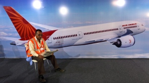 An Air India staff member reads a newspaper beside an image of a Boeing 787 Dreamliner in Hyderabad, India, on March 13, 2014. (Mahesh Kumar A.)