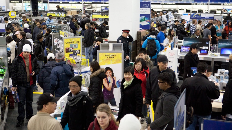 Shoppers scramble for merchandise inside a major electronic chain store in the early morning hours in Toronto on Boxing Day Monday, December 26, 2011.