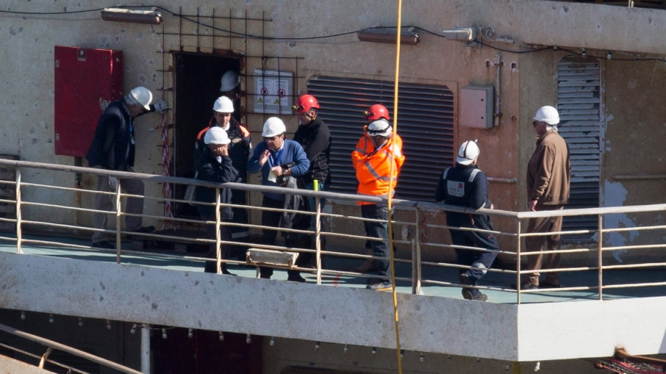Captain Francesco Schettino, fourth from left, talks on the upper deck of the wreck of the Costa Concordia cruise ship, just off the coast of the Giglio island, Thursday, Feb. 27, 2014. (AP / Andrew Medichini)