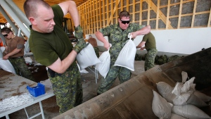 Military personnel from CFB Shilo work to fill and load sandbags in Portage La Prairie, Man., Saturday, July 5, 2014. (John Woods / THE CANADIAN PRESS)